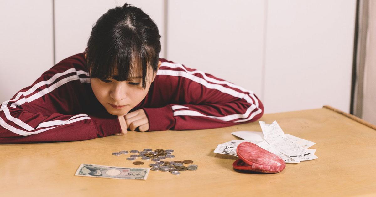 お金を見つめる女性